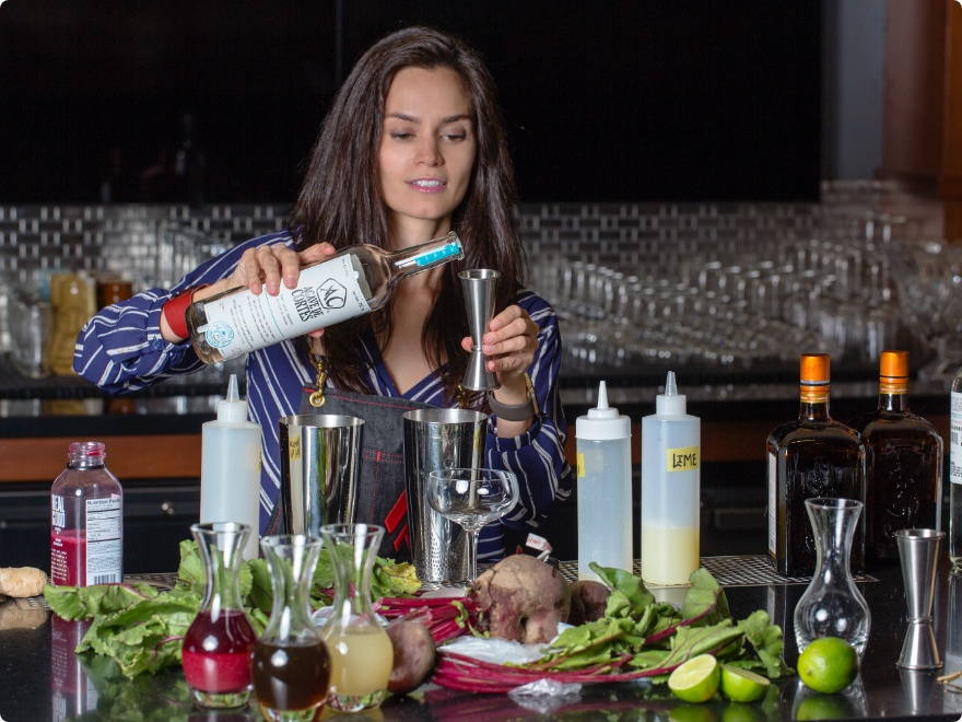 female mixologist pours alcohol into a jigger at a bartop with juices, alcohols, fruits, vegetables and glassware