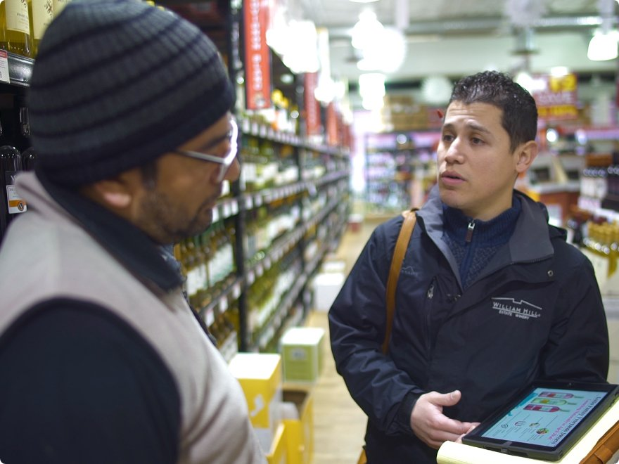 salesman with a tablet talks with a customer at a liquor store