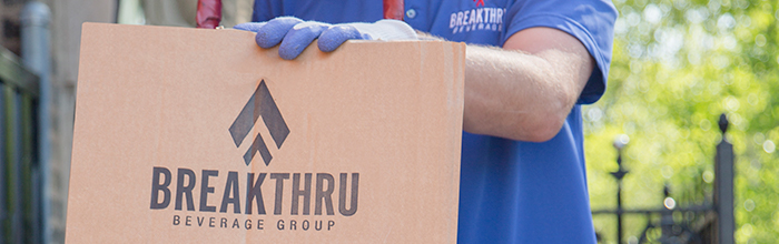 blue gloved hand resting on a cardboard packaging box with a Breakthru Beverage Group logo