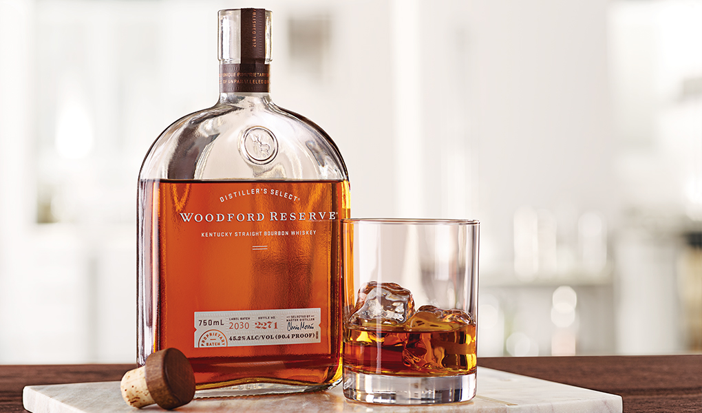 Golden Brown Bottle of Woodford Reserve perched on table with a white splash background