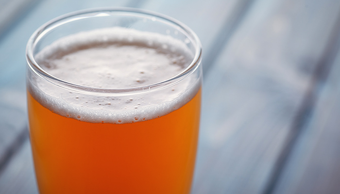 hazy orange beer closeup with a blurred wooden table backdrop