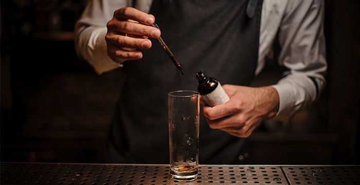 mixologist dripping bitters into an empty highball cocktail glass on a steel counter
