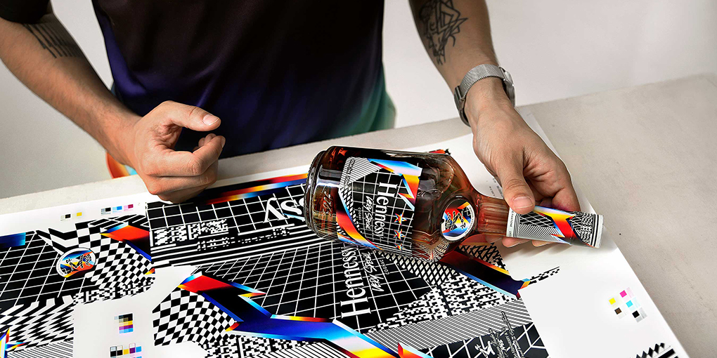 Artist Felipe Pantone holds his V.S. Limited Edition Hennessy bottle