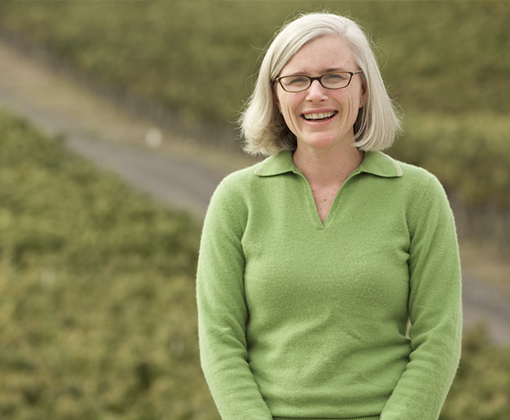 blonde hair woman with glasses wearing a green sweater standing in a vineyard