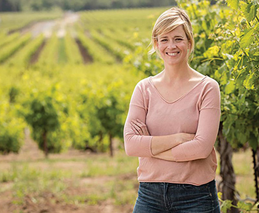 smiling blonde-haired woman in a pink shirt standing in a vineyard
