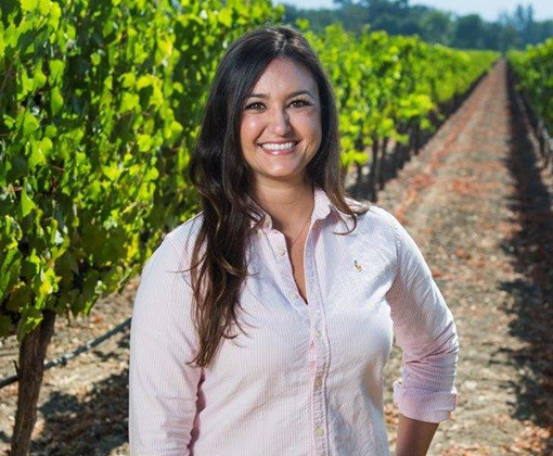 brunette woman in a rose-colored blouse standing in a green-leafed vineyard