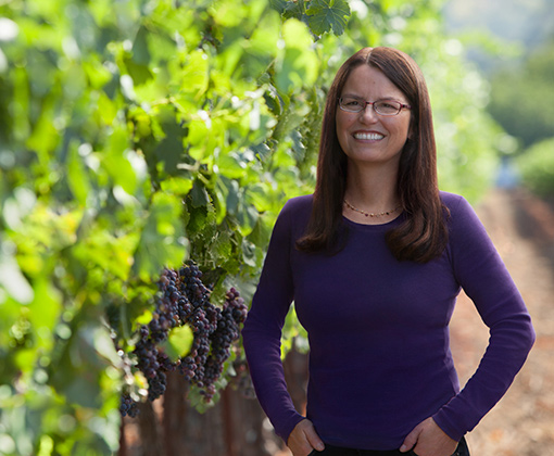 woman with glasses wearing a violet shirt in a green-leafed vineyard