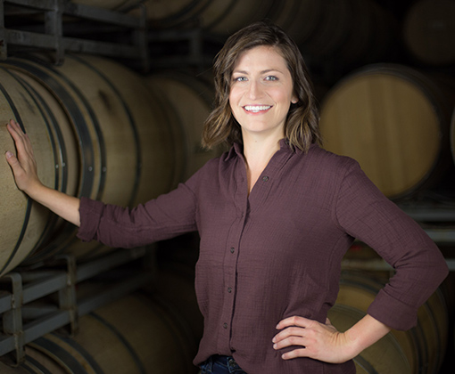 pale skin brunette woman with maroon shirt in a room of stacked barrels
