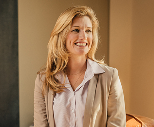 smiling blonde-haired woman in a tan suit jacket in a beige room