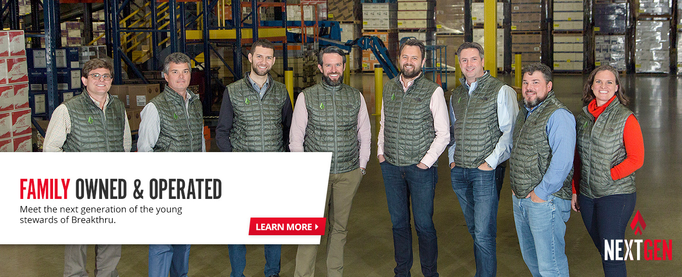 group of people in a warehouse wearing grey vests